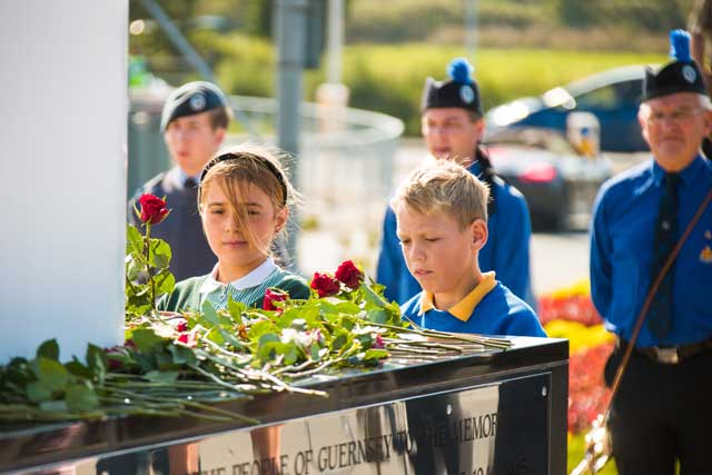 Two of the 36 children from the Forest Primary and Le Rondin School placing a single red rose around the memorial one for every man named.